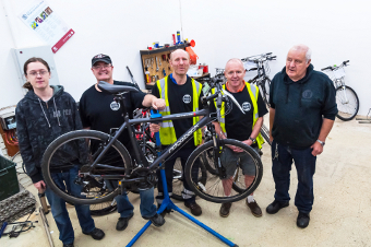 ON YER BIKE – volunteers Ryan Brown, David Vanstone, Steve Payne, Fred Jenkin and Mike Burger set up the bike repair shop in Sheerwater