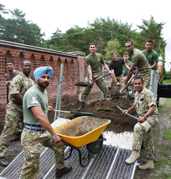 MUCKING IN – Army volunteers get down and dirty in the renovation process