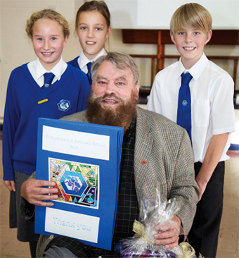 OVERWHELMED – Taryn Bennett and Daisy Dunleavy, both 10, and Michael-Lee Hutt, 11 hand Brian presents from the school