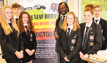 THE HEAT IS ON – Levi Roots with lucky students Charlotte Hague, Luke Bunyan, Ella Zimmerman, Iona Preston, Molly Robinson, Max Eicke, Dan Byrne and Jake Waller