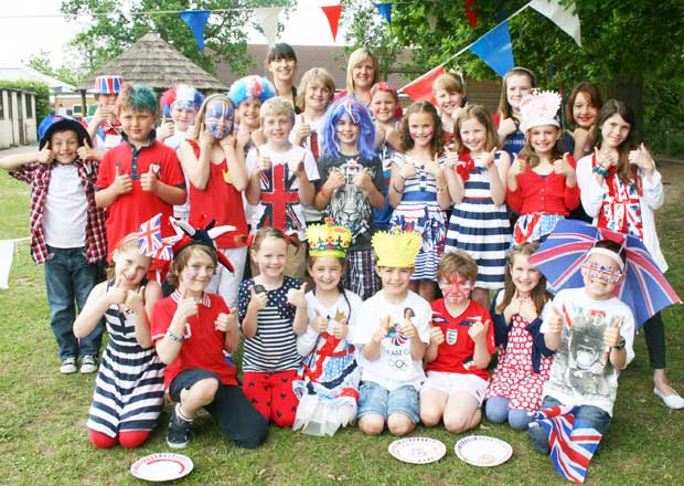 IN THE RED, WHITE AND BLUE CORNER – pupils at Hermitage School, St Johns, give their Jubilee celebrations the thumbs up