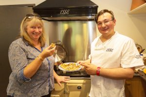 Chef Daniel Blewitt (Esse Southern Sales Rep) demonstrates the Esse EC2i Range Cooker to Erica Bomphrey from Bisley.
